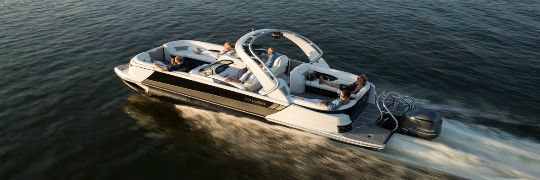 sylvan pontoon, 3 by 1 ratio, speeding, white interior, mostly white exterior, black and tan panel on side